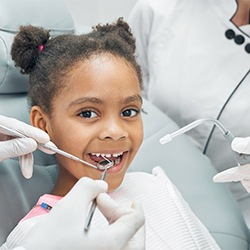 Young, happy girl receiving checkup from dentist in Greeley