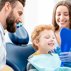 Child patient checking smile in mirror with mother and dentist in Greeley