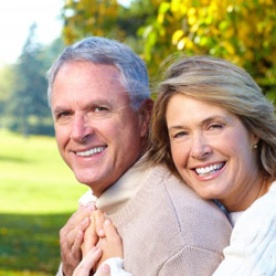 An older couple with dental implant supported replacement teeth smiling outside
