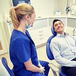 a man in dental chair smiling after dental implant tooth replacement