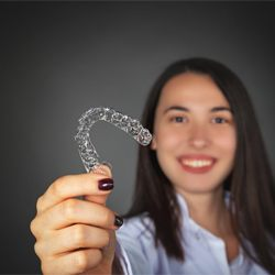 A young woman holding a clear Invisalign aligner