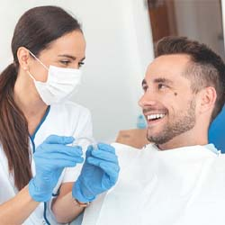 A young woman smiling after Invisalign treatment