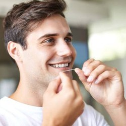 Man flossing teeth after porcelain veneer placement