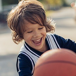 Smiling young boy playing basketball