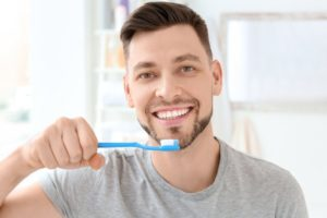Man smiling while using brushing tips from dentist in Greeley