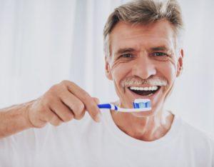 older man brushing his dental implants in Greeley